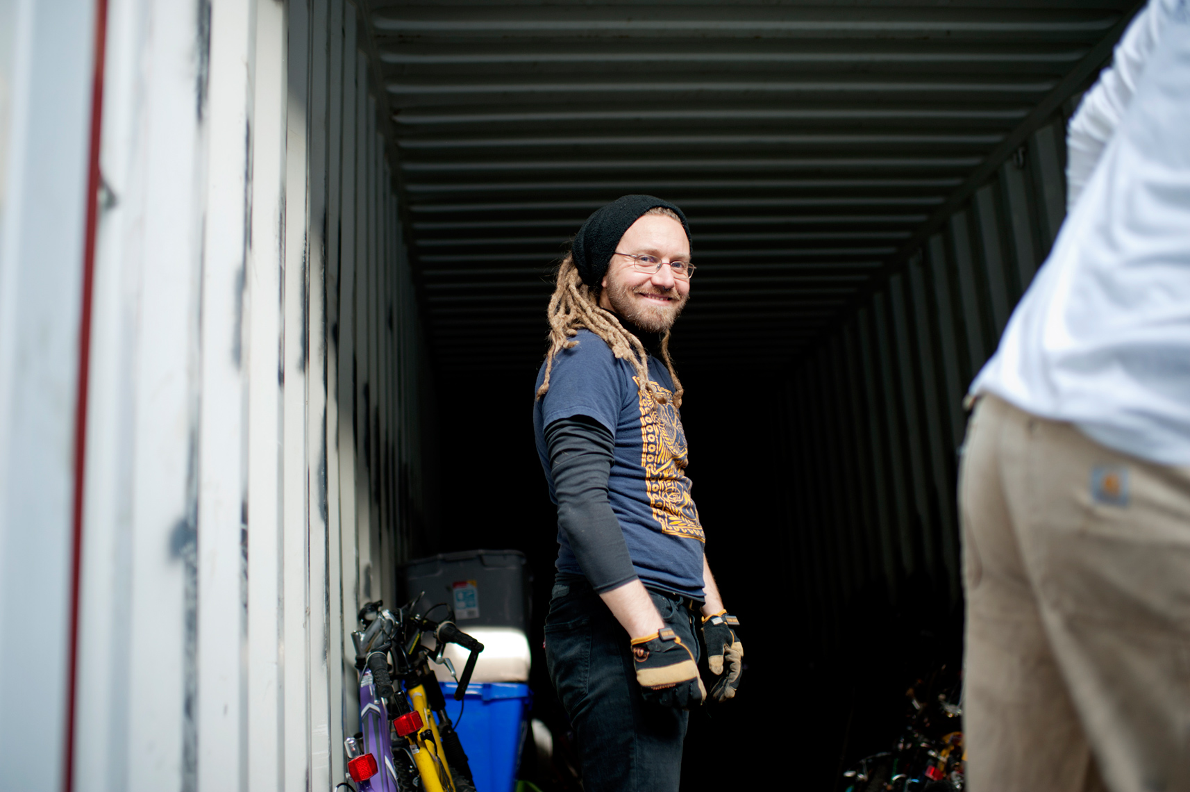 Bikes Not Bombs volunteer packing reclaimed bikes into shipping container to ship to Nicaragua