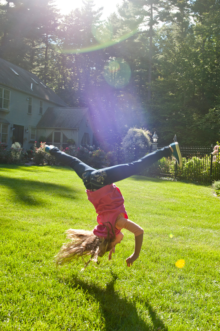 girl doing cartwheel living the rural life in Western Massachusetts for the Boston Globe