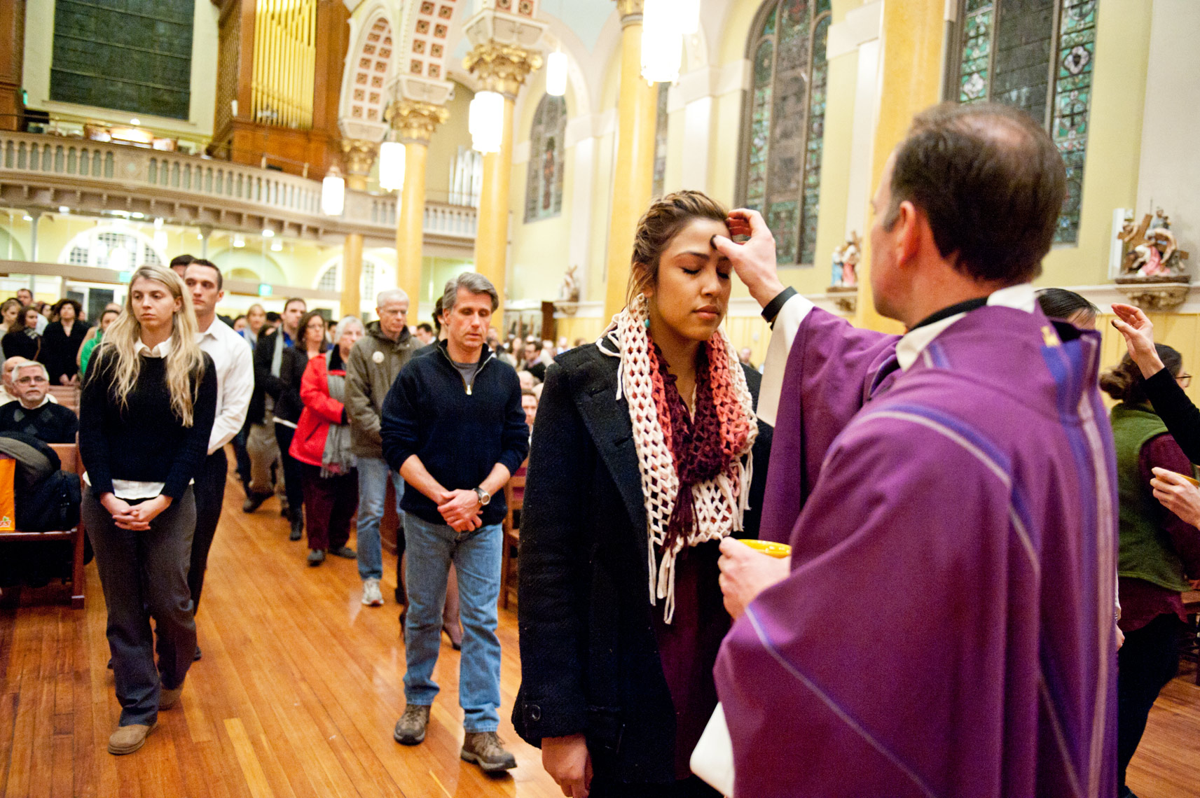 the Reverend John Unni placing repentance ashes on foreheads of parishioners St. Cecilia Parish Ash Wednesday