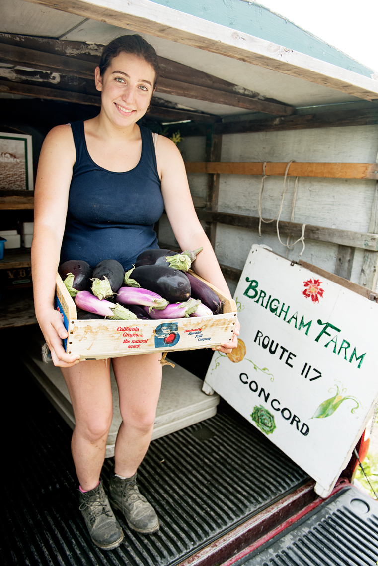 young woman unloading vegetables for Brigham Farm
